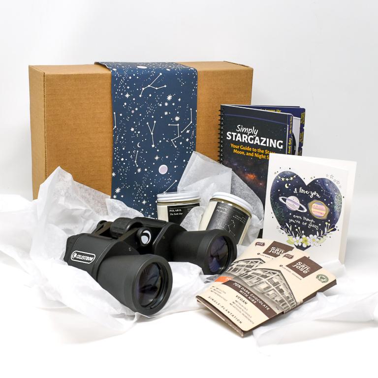 Gift box with greeting card, binoculars, chocolate and book