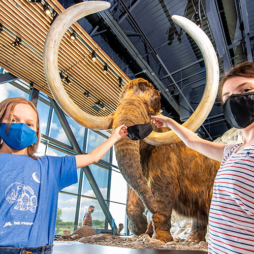 Kids holding face mask up to woolly mammoth