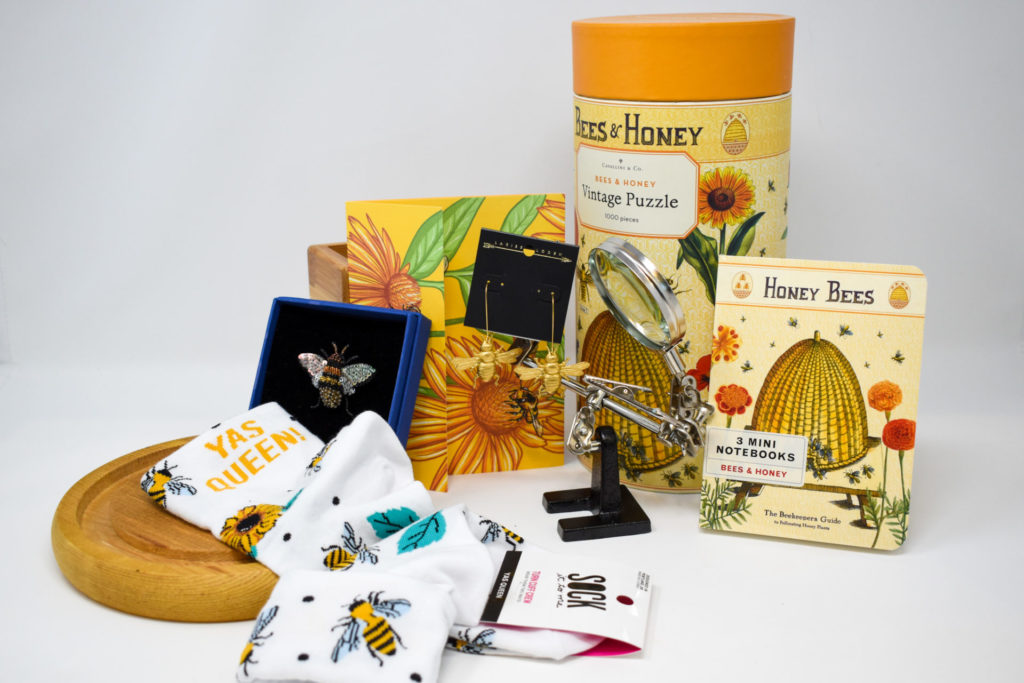 An arrangement of bee themed gifts including a puzzle, notebooks, socks, earrings, and a pin