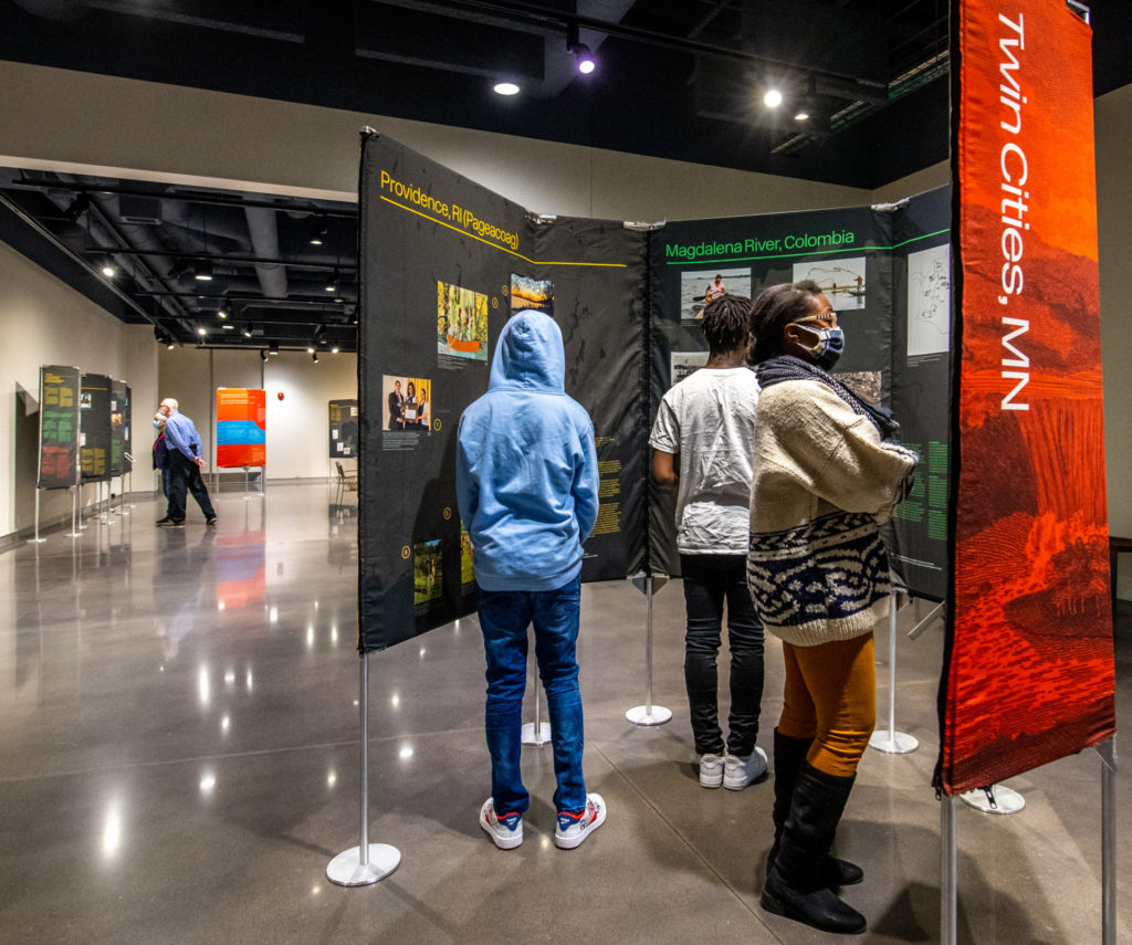 A group of people looking at a multisided panel with text and images about environmental justice