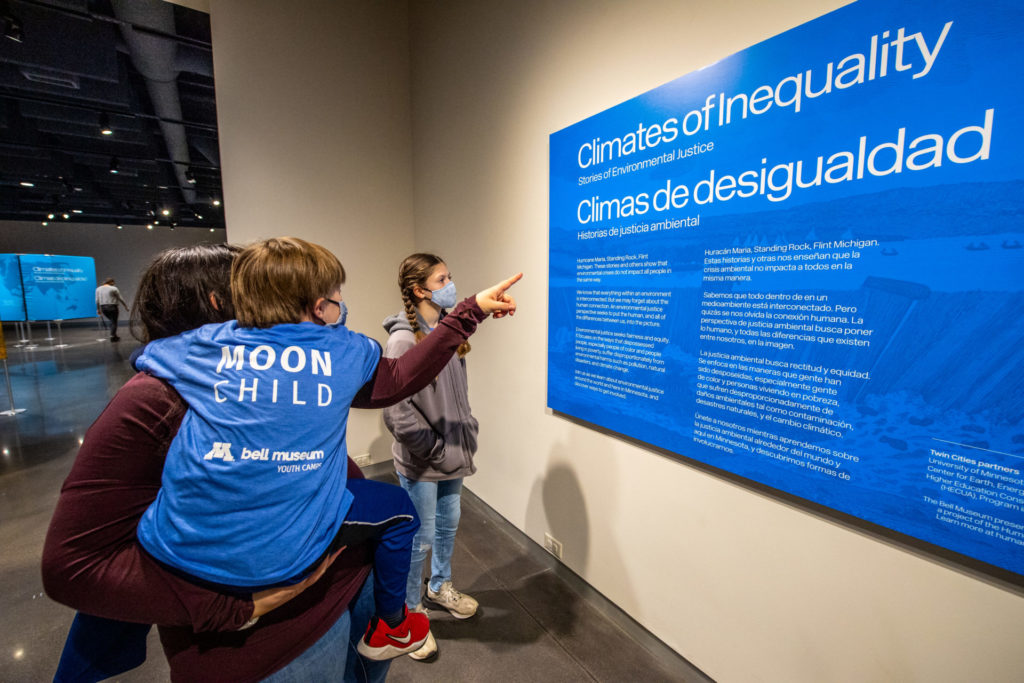 """A family pointing at a sign that says """"Climates of Inequality"""""""