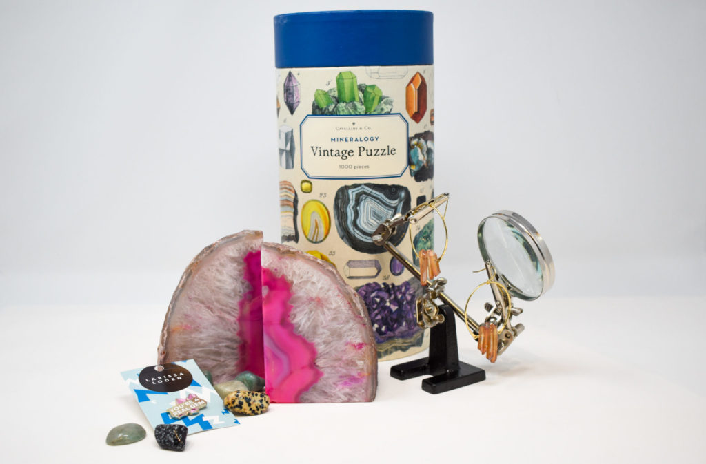 An arrangement of mineral-themed gifts, including bookends, earrings, a pin, and puzzle
