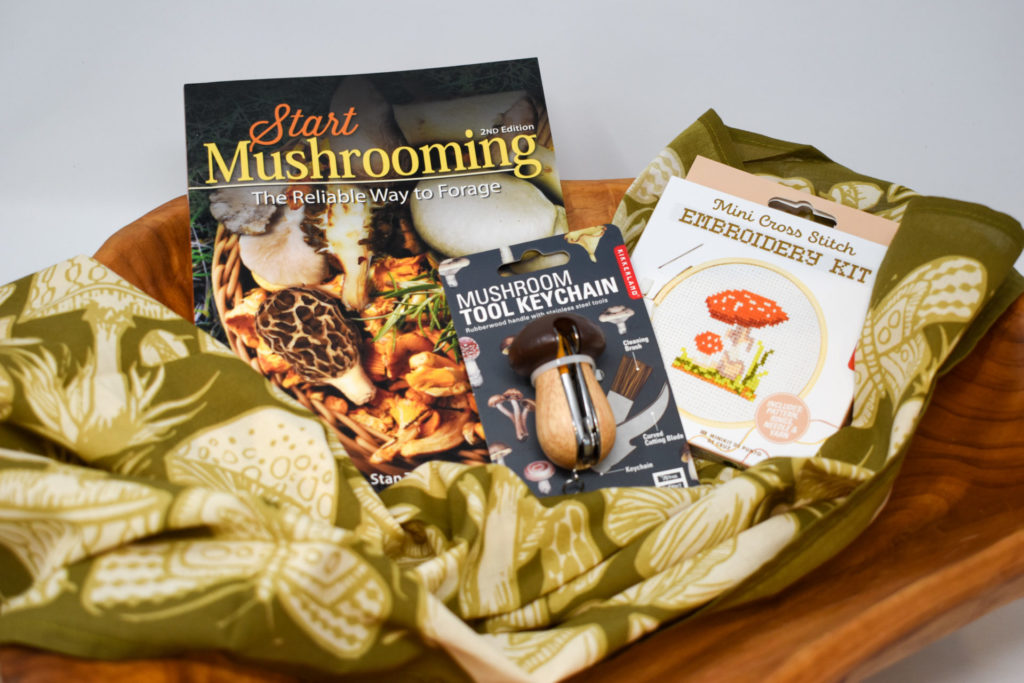 An arrangement of mushroom-themed gifts, including a book, an embroidery kit, a tool, and a scarf