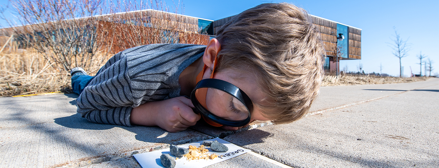Child looking at group of rocks on sidewalk through magnify glass