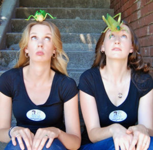 two women sitting with grasshoppers on their head