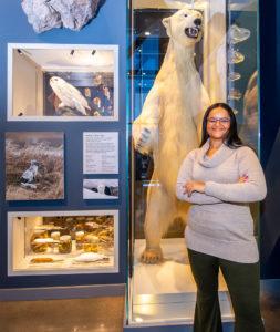 Woman standing next to polar bear display