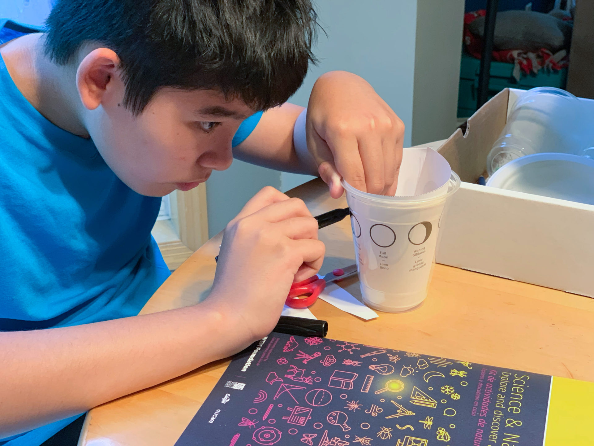 Child marking a plastic cup