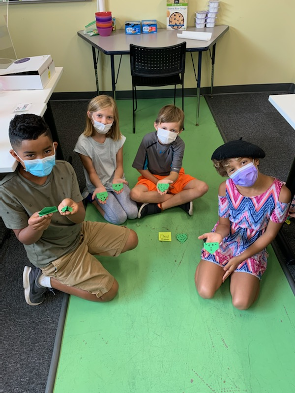 Four children with masks showing off their origami frog