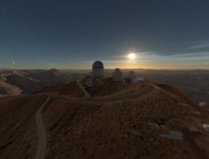 Three telescopes on top of mountain facing the sun