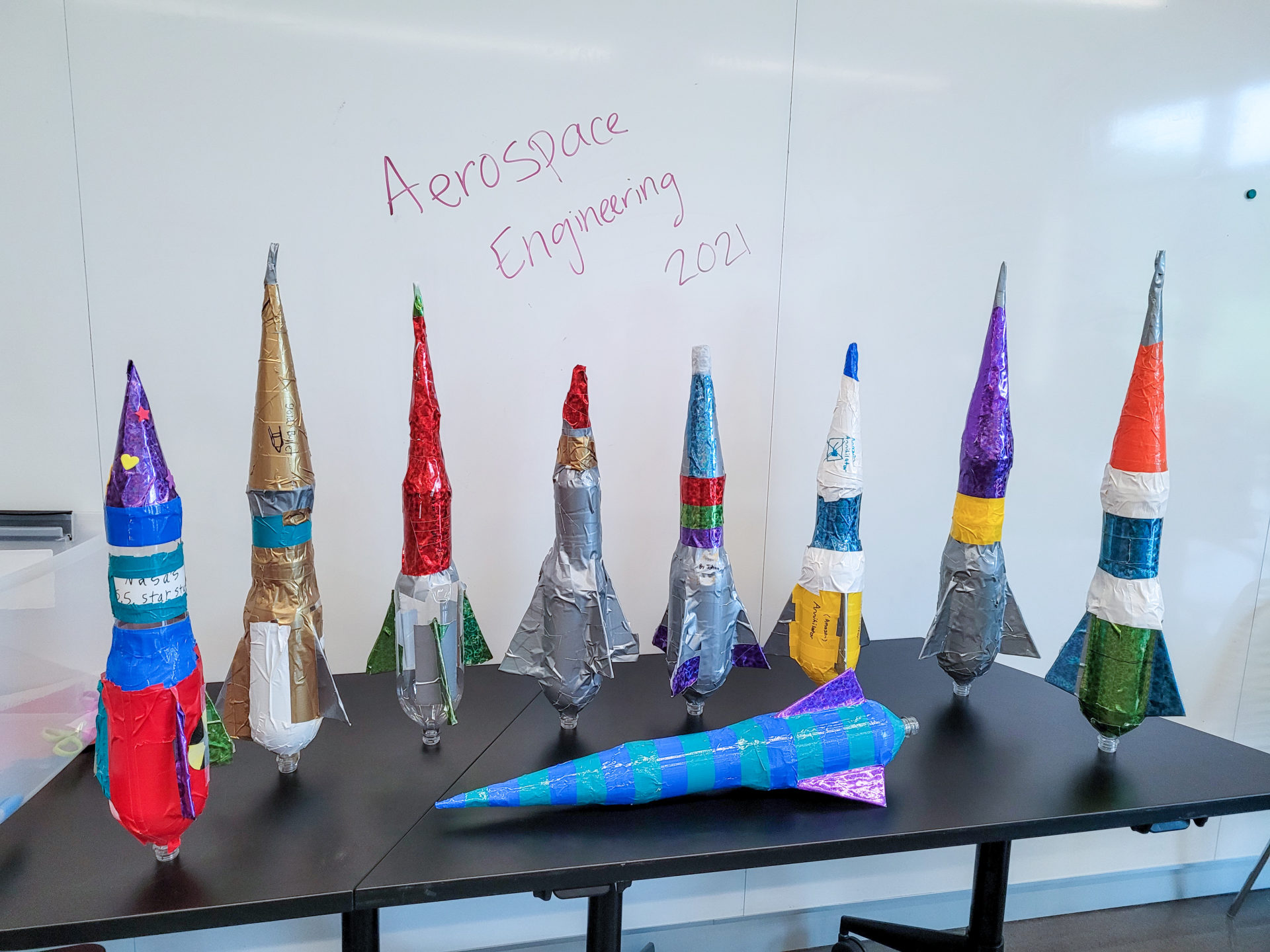 9 bottle rockets on a table in front of text that reads: Aerospace Engineering