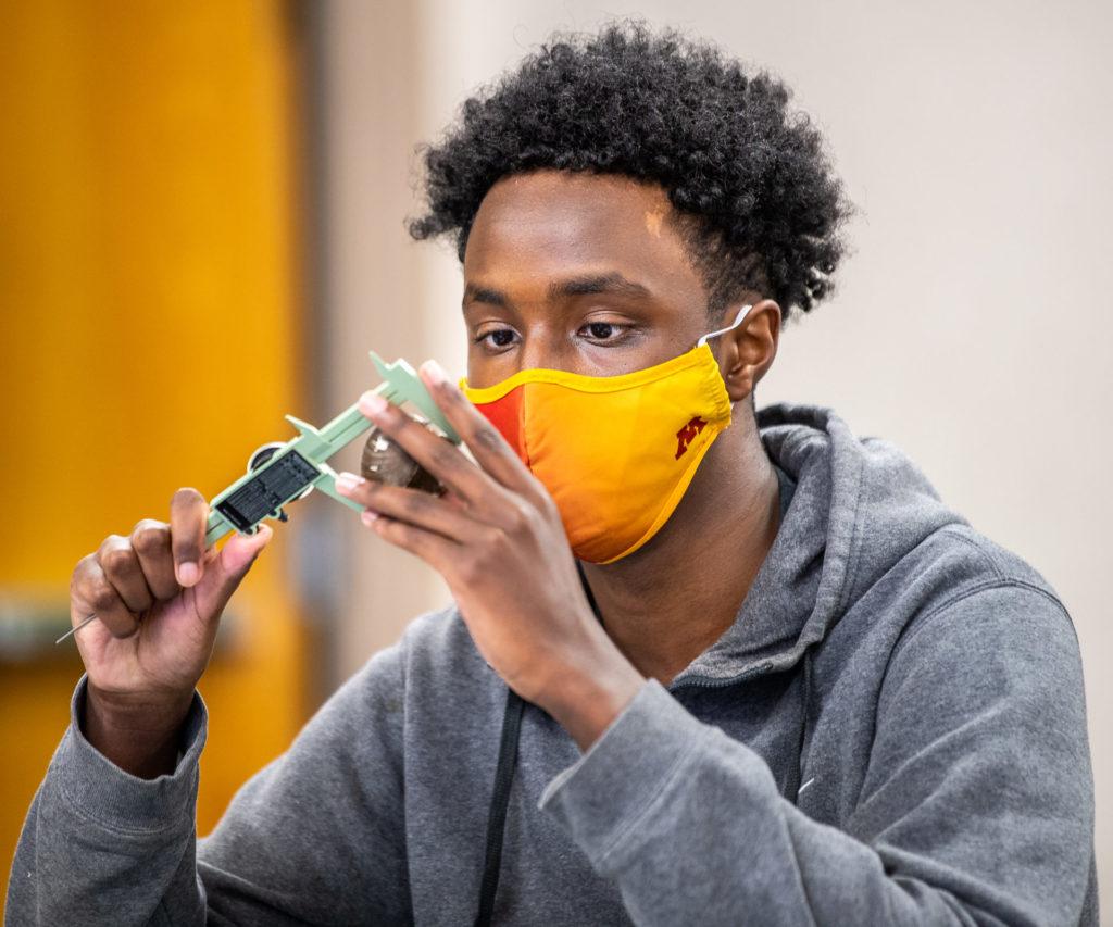 A high school intern measuring a bird