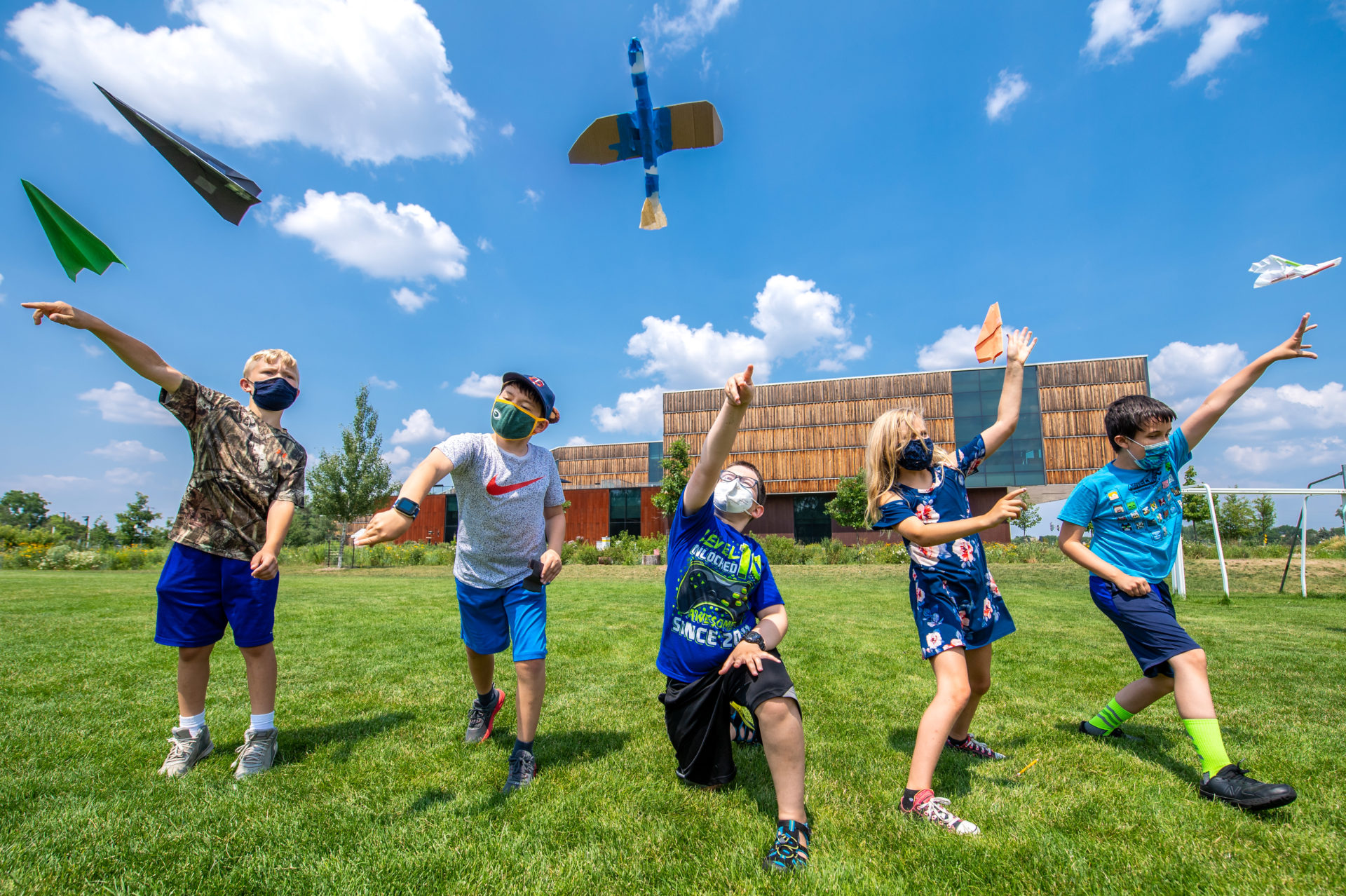 5 Children flying model and paper planes outside on grassy field