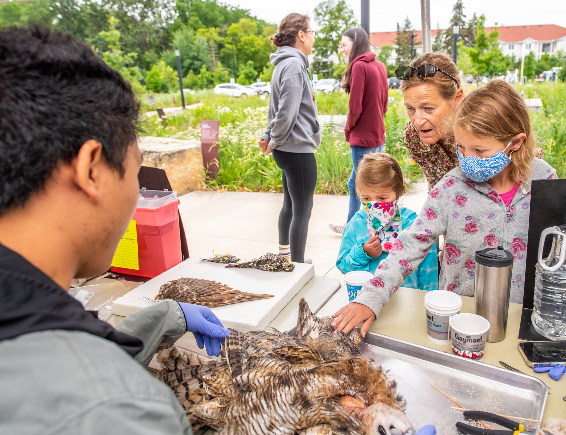A family touching an owl skin at Expeditions to the Bell