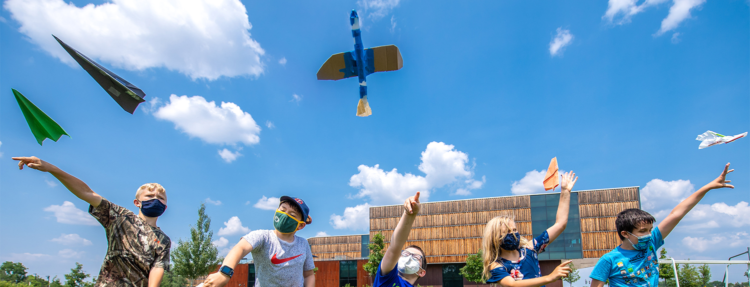 Five children flying paper and model airplanes