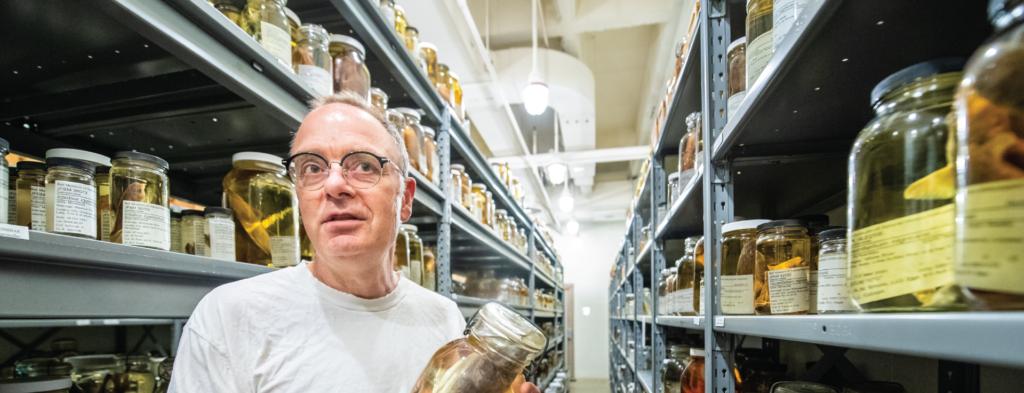 Andrew Simons holding fish specimen in an aisle full of fish specimen