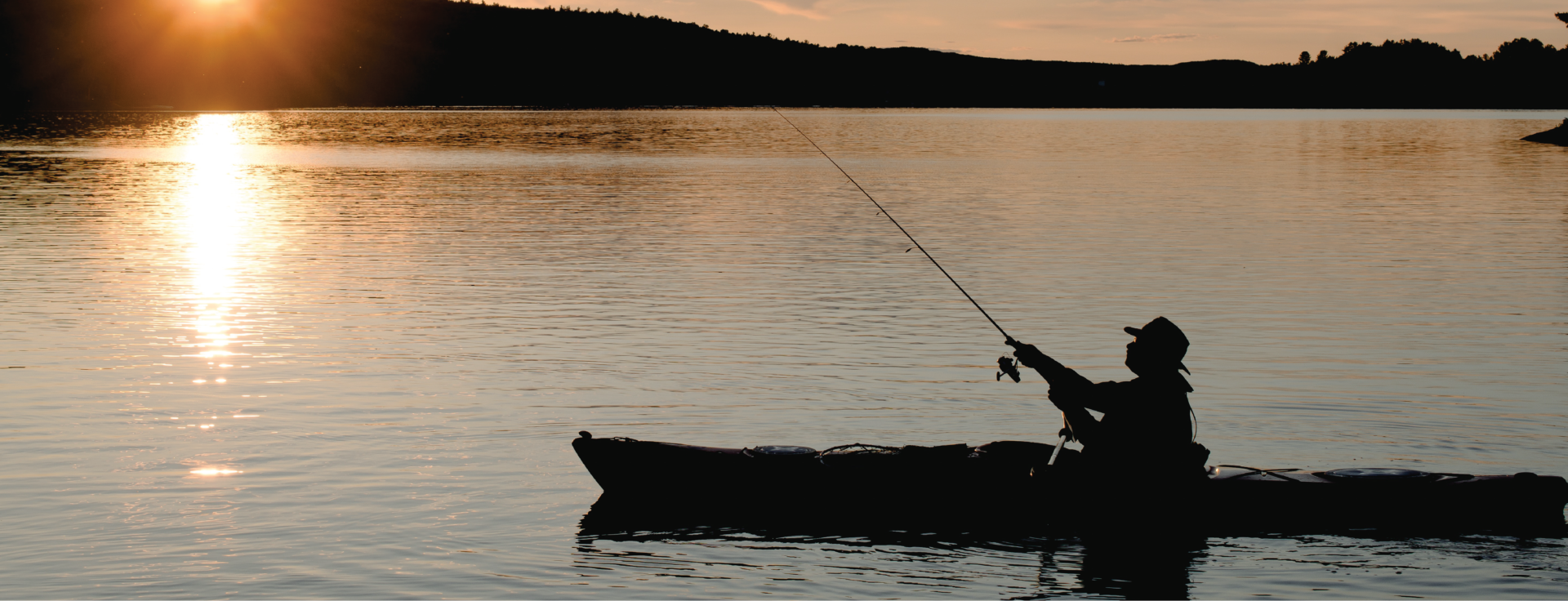 Silhouette of one person in a boat fishing in the middle of lake
