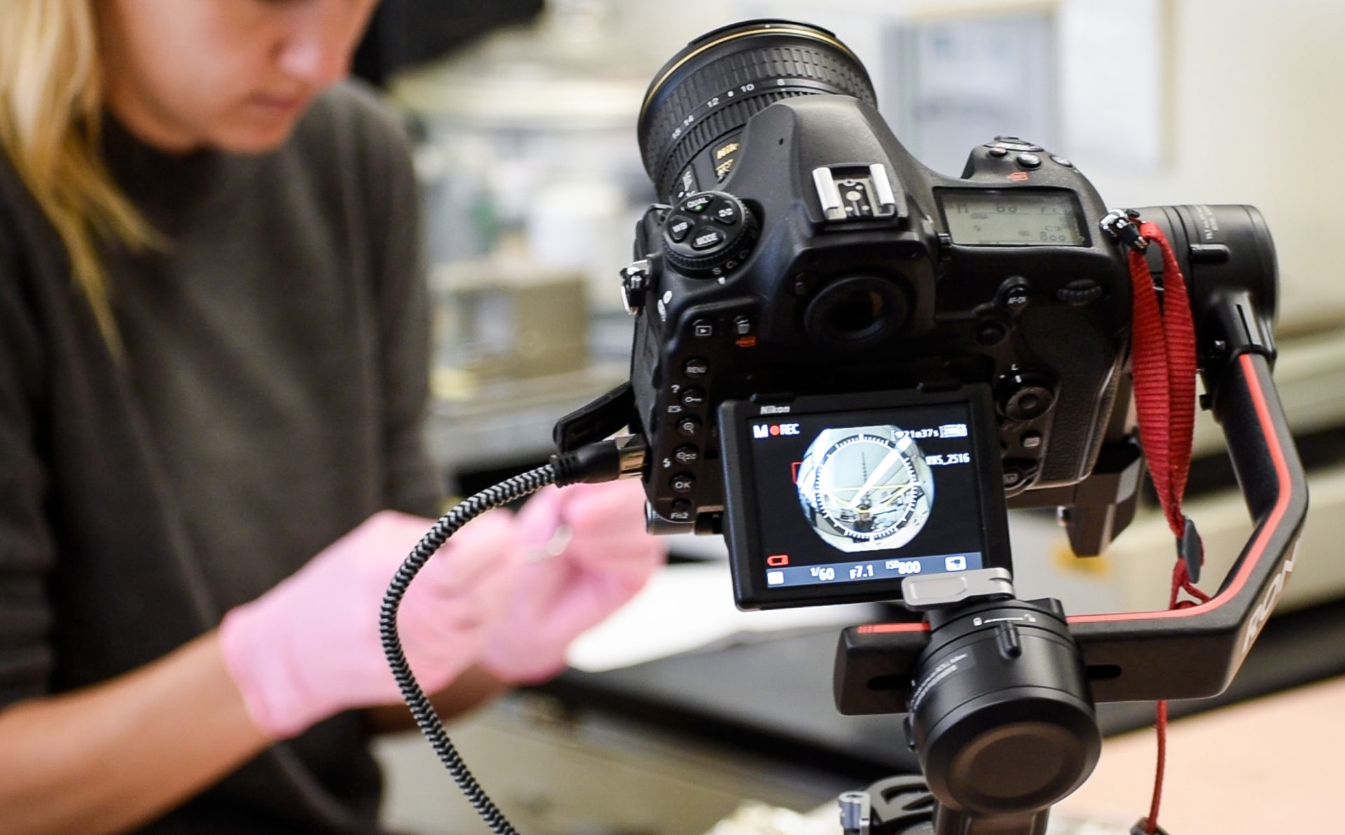 A camera with a wide angle lens filming a scientist