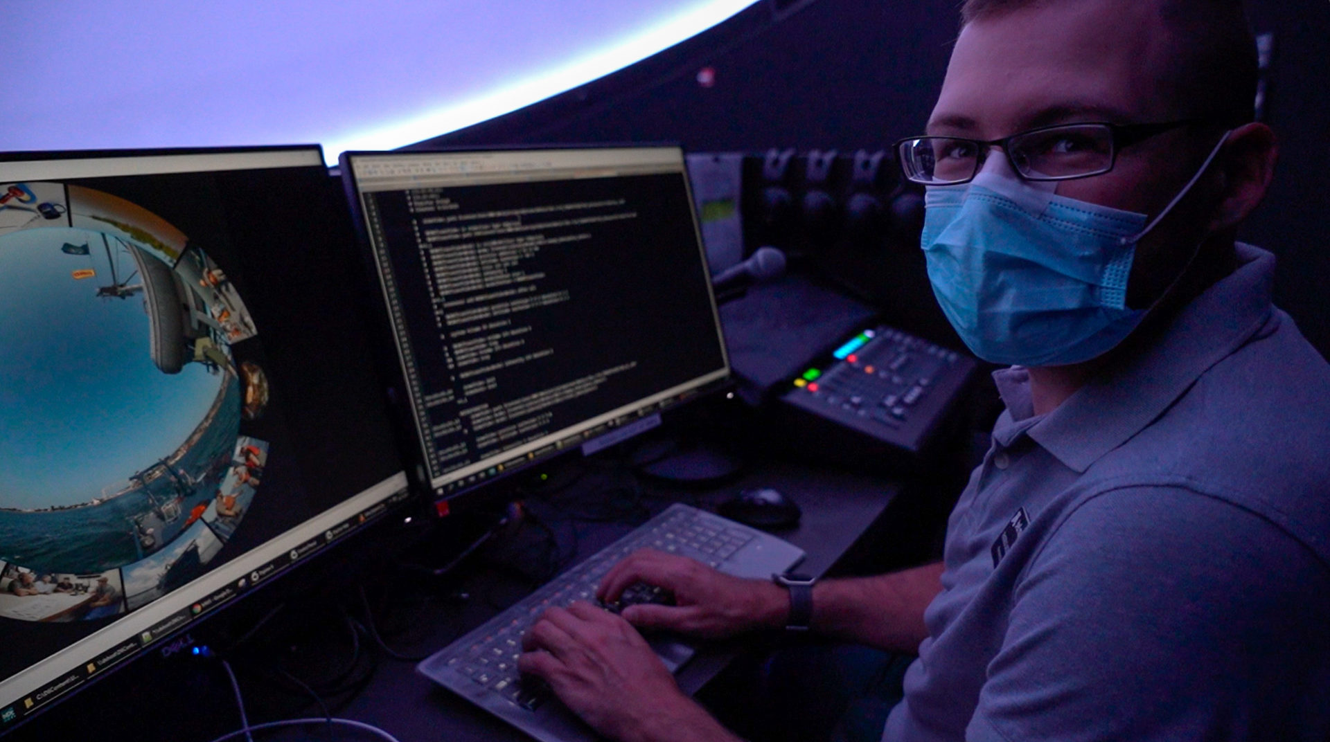 A person with a mask on sits at a computer to present a planetarium show